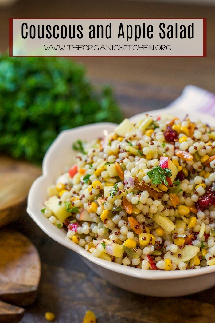 A pretty bowl of Couscous and Apple Salad on a wood surface with a bunch of parsley in backgraound