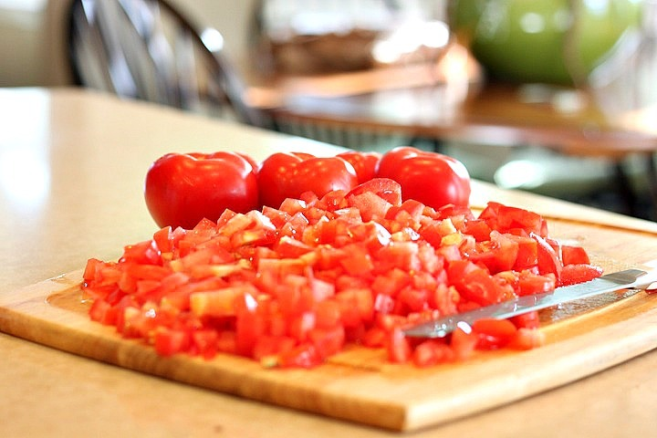 Fresh tomatoes diced on a cutting board: Creamy Carrot Tomato Soup: Comfort Food at it's Finest