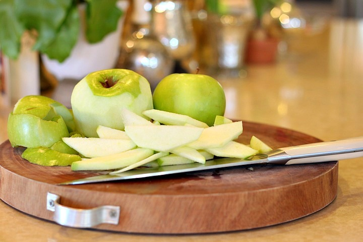 Sliced granny Smith apples and knife on a cutting board