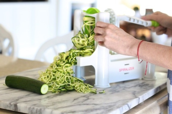 A woman's demonstrating how to make zoodles for Almond Pesto Zucchini Noodles