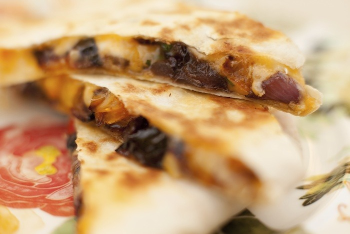 Caramelized Vegetable Quesadillas with black beans on colorful plate