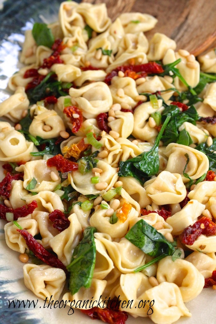 Three Cheese Tortellini with Spinach and Sun Dried Tomatoes garnished with pine nuts