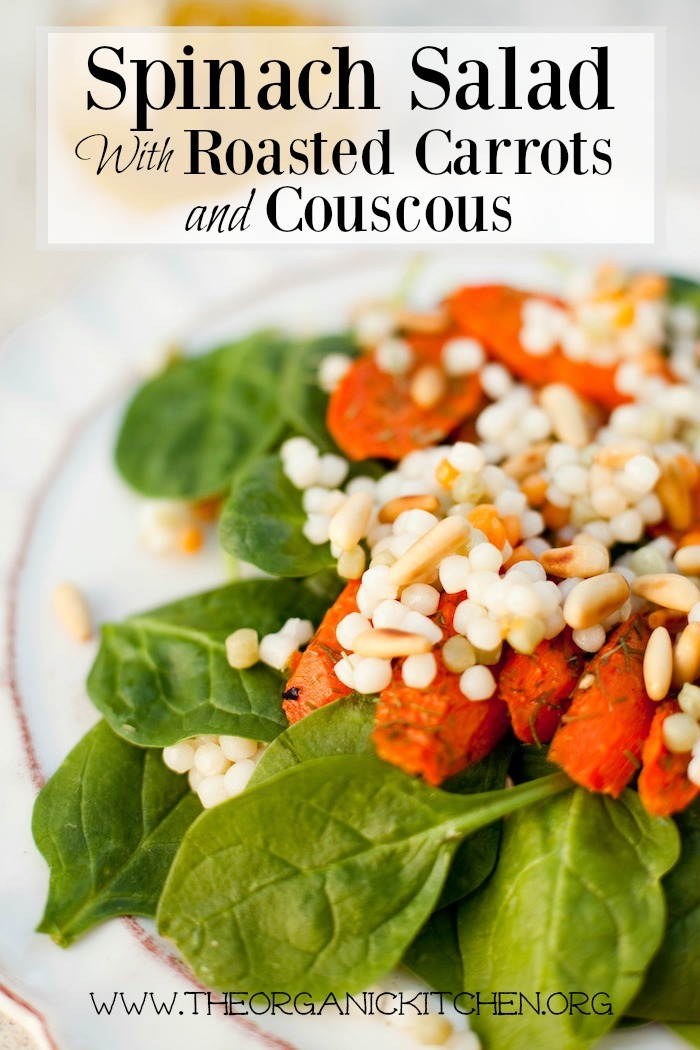 Baby Spinach Salad with Roasted Carrots and Israeli Couscous on white plate with scalloped edges