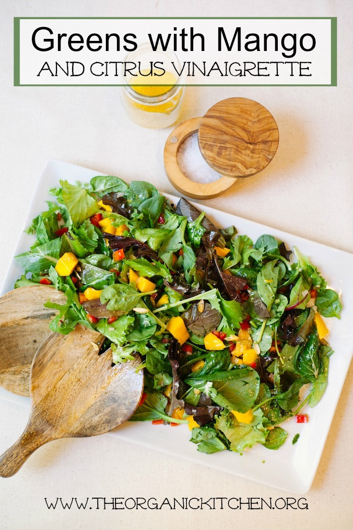 Greens with Mango and Citrus Vinaigrette on a large white platter with a jar of salad dressing and a bowl of sea salt