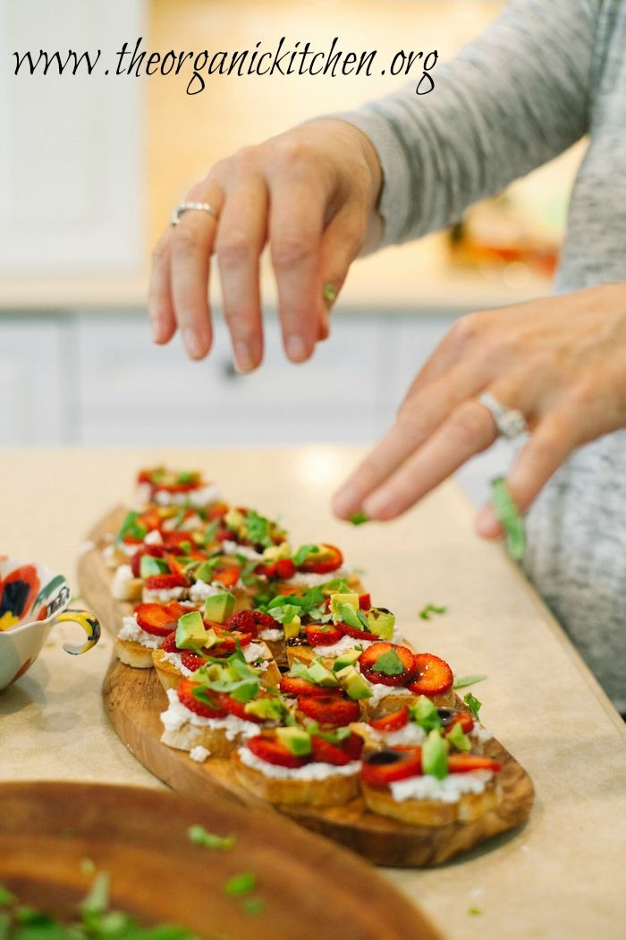 A woman garnishing Strawberry and Avocado Bruschetta with basil