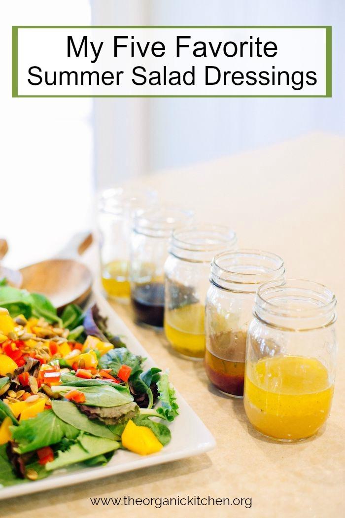 Mason jars with my Five Favorite Summer Salad Dressings on a counter alongside a mango salad