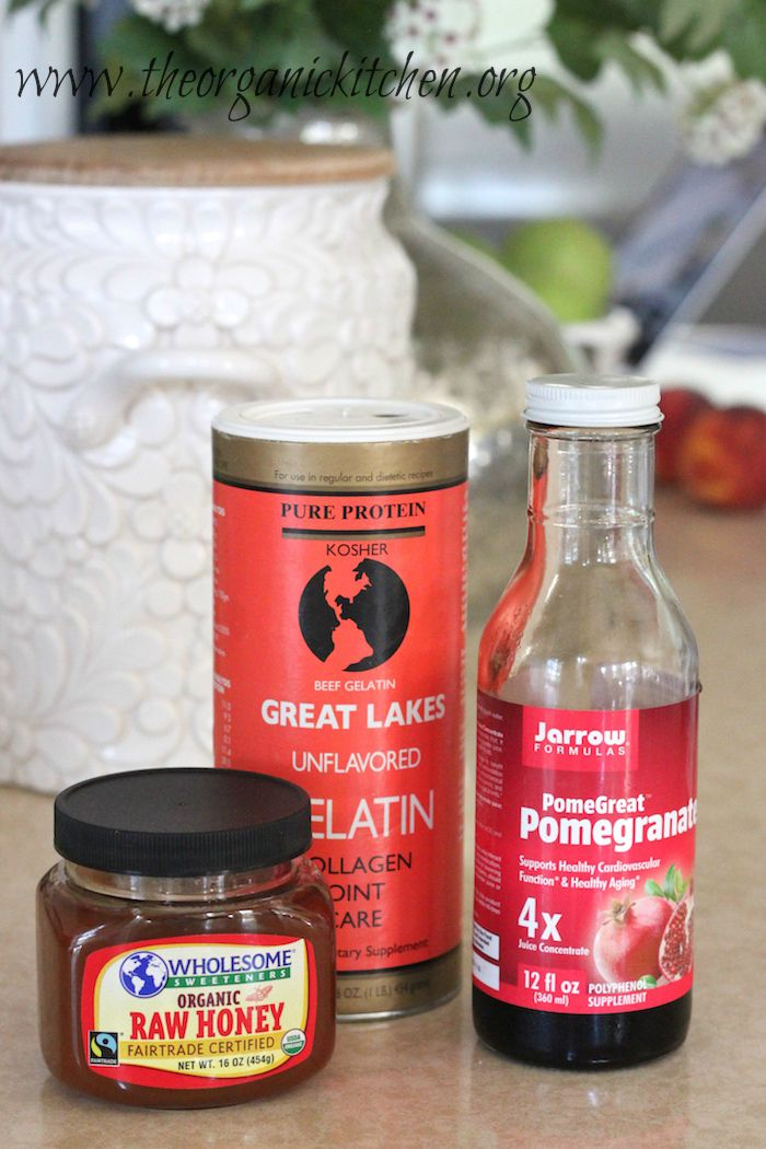 The ingredients for Pomegranate Gelatin Gummies: a jar of raw honey. a container of gelatin and pomegranate syrup