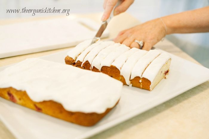 Hand slicing Lemon Vanilla Raspberry Cake loaf
