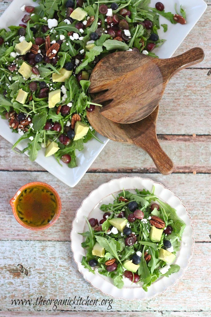 Blueberry and Avocado Salad on white dishes with a small bowl of salad dressing on a light green wooden backdrop