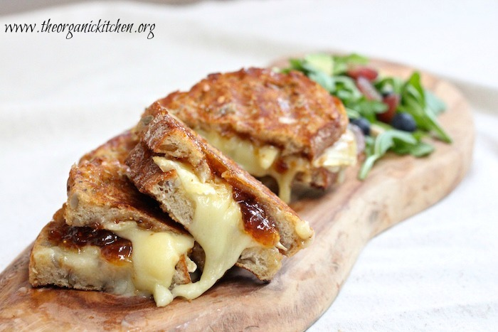 A close up of three Brie and Fig Grilled Cheese sandwiches served on a wooden platter with salad