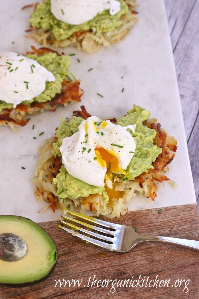 """Three Potato Avocado """"Toast"""" With Perfectly Poached Eggs , one with runny yolk, on a cutting board"""