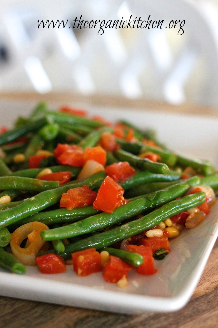 Grandma Julia's Green Beans: Green beans, tomatoes, pine nuts and onions on a white platter