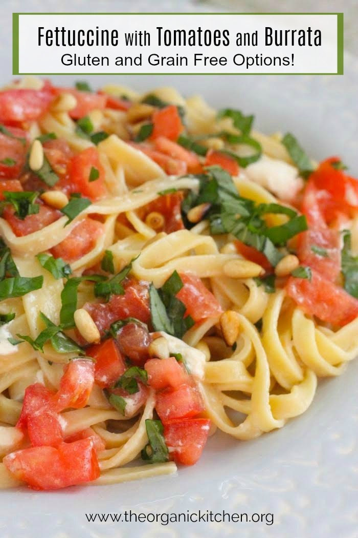 Fettuccine with Tomatoes and Burrata Cheese garnished with basil and pine nuts on light blue plate