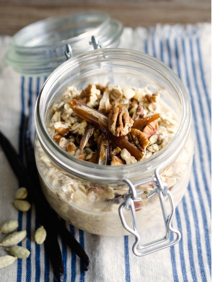 A mason jar filled with Grab and Go Maple Vanilla Overnight Oats topped with pecans
