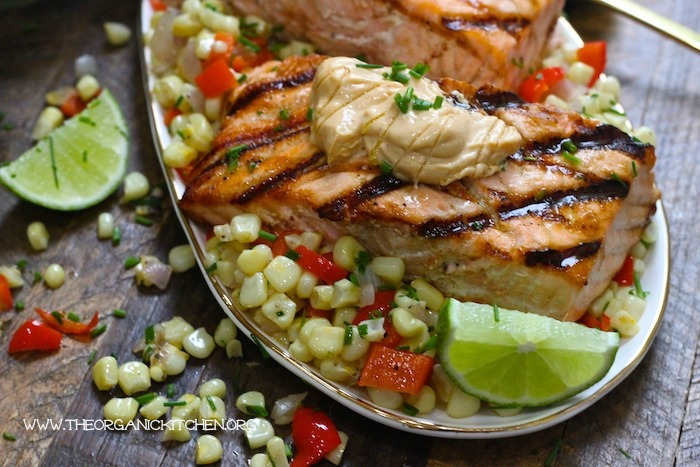 Salmon with Corn Hash and Chipotle Lime Mayo garnished with lime wedges and chives