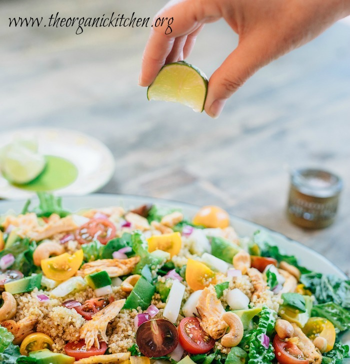 A woman's hand squeezing a lime wedge onto the Easy Blackened Chicken and Quinoa Salad