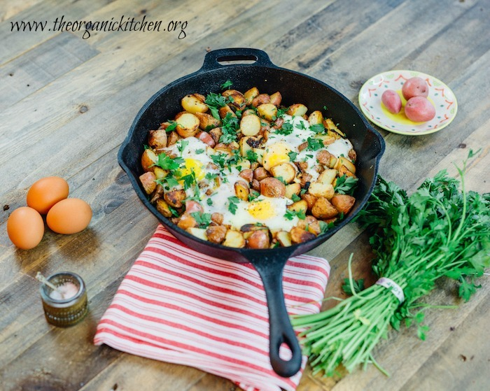 Crispy One Pan Potatoes with Eggs in a cast iron skillet surrounded by eggs, sea salt, and fresh herbs