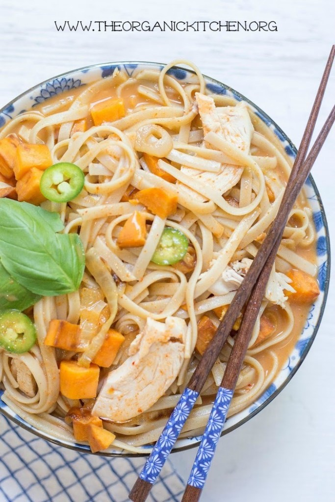 A large bowl of Chicken and Sweet Potato Asian Noodle Soup with chopsticks resting on top