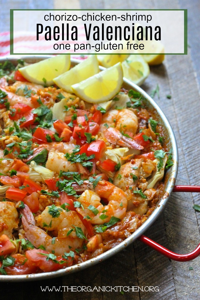 Paella Valenciana with Chicken, Chorizo and Shrimp garnished with lemon wedges in a paella pan