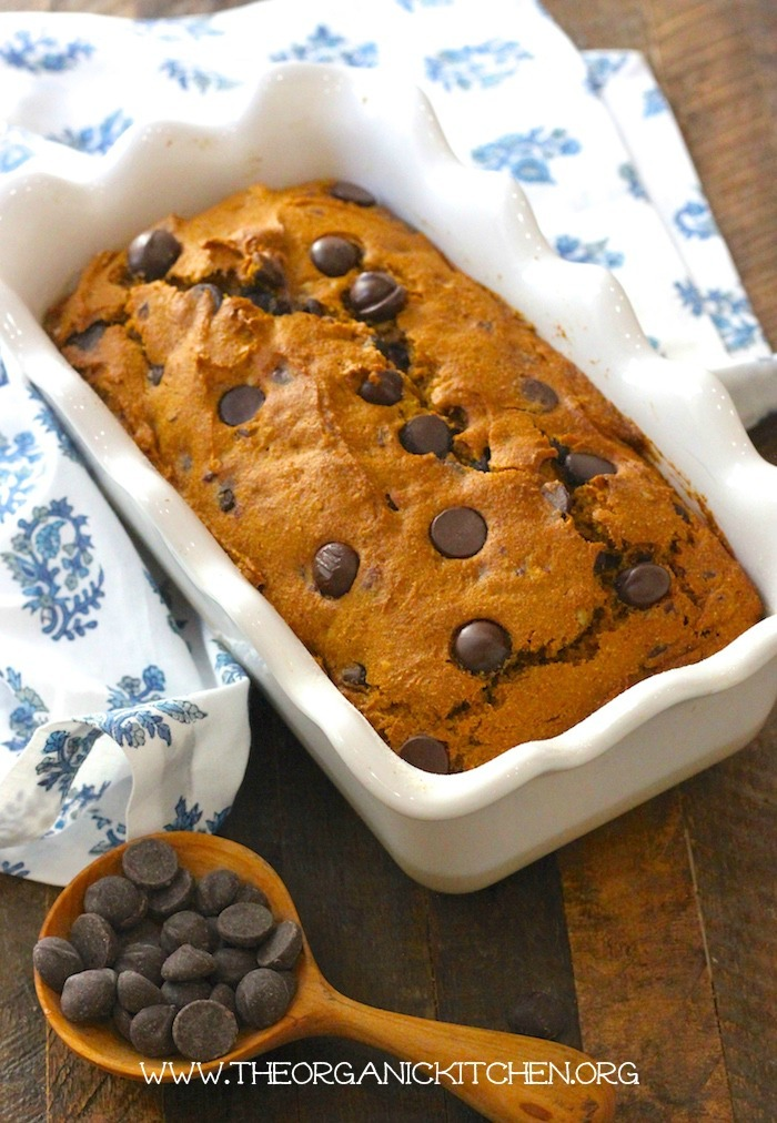 Chocolate Chip Pumpkin Pecan Bread in a white baking dish set on a wood table with a small wooden spoon full of chocolate chips