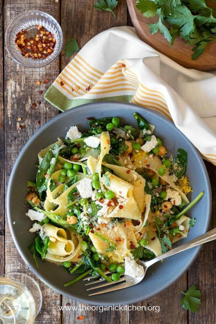 A blue bowl filled with Pappardelle with Wilted Greens (Gluten Free Option) and surrounded by greens, pepper flakes and a napkin