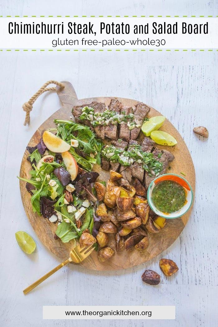 Le Chimichurri Steak, Pommes de Terre et Salade Board sur une surface en bois blanc décorée d'une fourchette dorée et de quartiers de citron vert