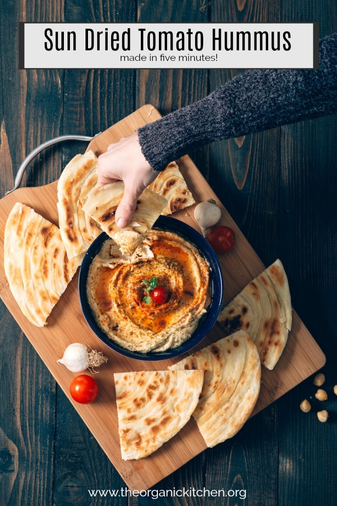 A woman's hand dipping pita bread into Sun Dried Tomato Hummus