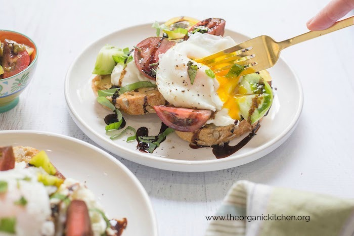 A fork piercing the yolk Heirloom Tomato Burrata Toast with Poached Eggs