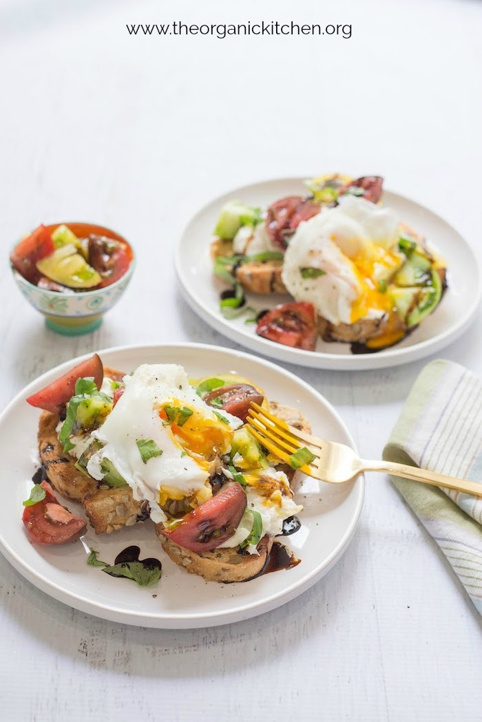 Two plates of Heirloom Tomato Burrata Toast with Poached Eggs on a white table