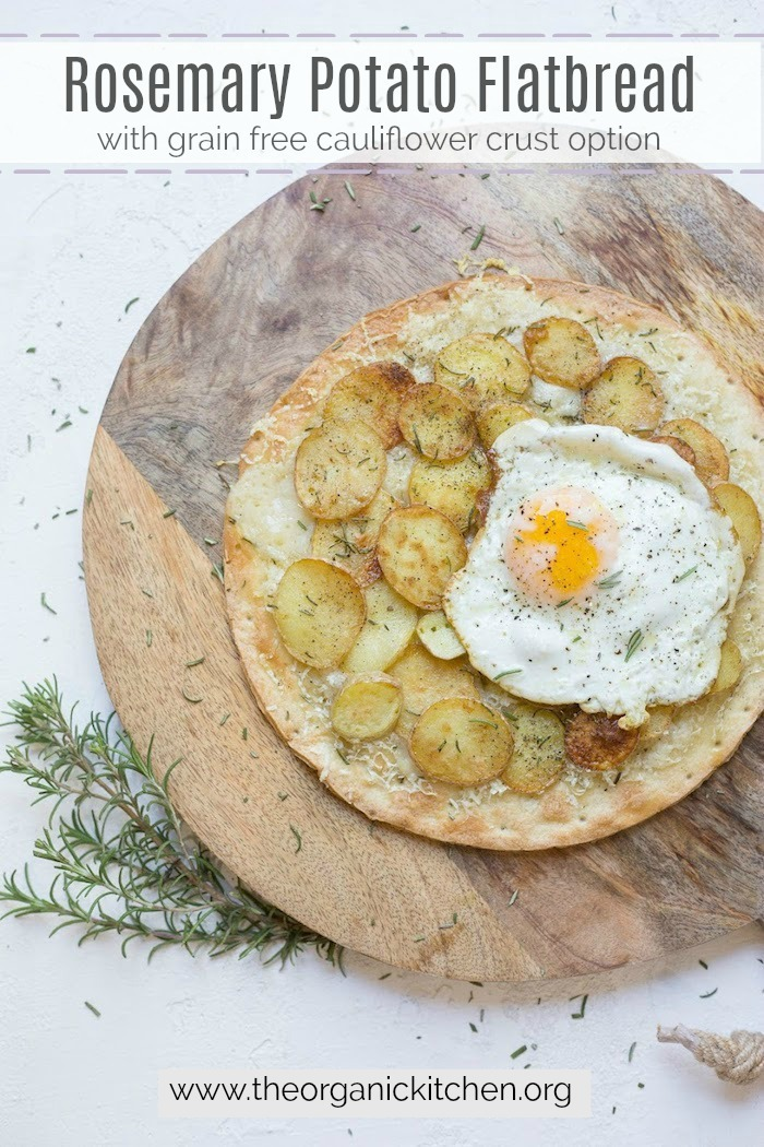 Rosemary Potato Flatbread with Cauliflower Crust Option topped with a fried egg on a wooden board