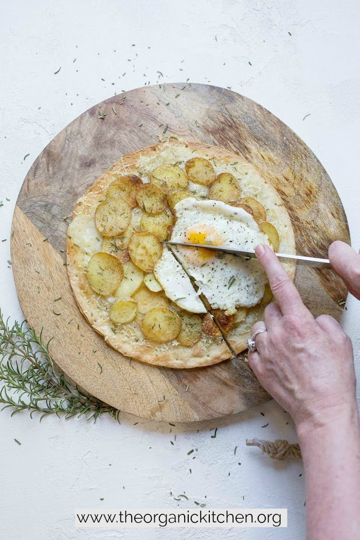 Hands holding a knife and cutting a slice of Rosemary Potato Flatbread with Cauliflower Crust Option