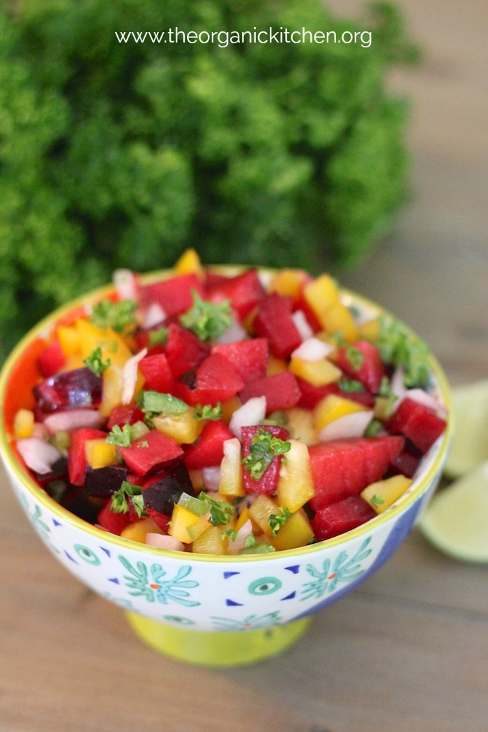 A small bowl of plum salsa on a wood table with lime wedges and cilantro