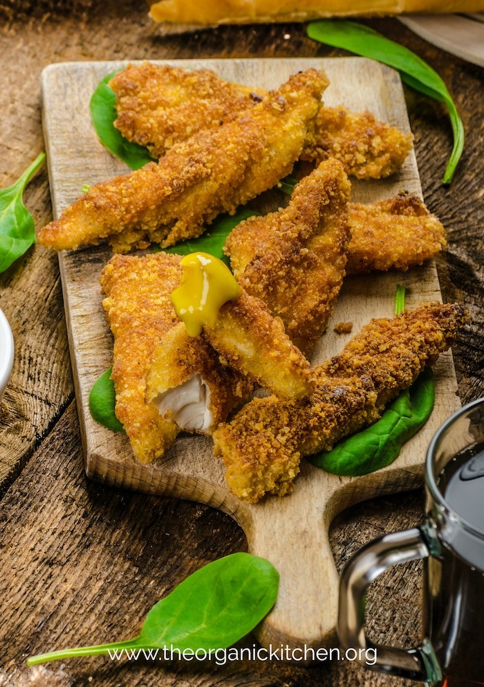Keto-Paleo-Whole30 Easy Chicken Tenders garnished with greens on wooden table