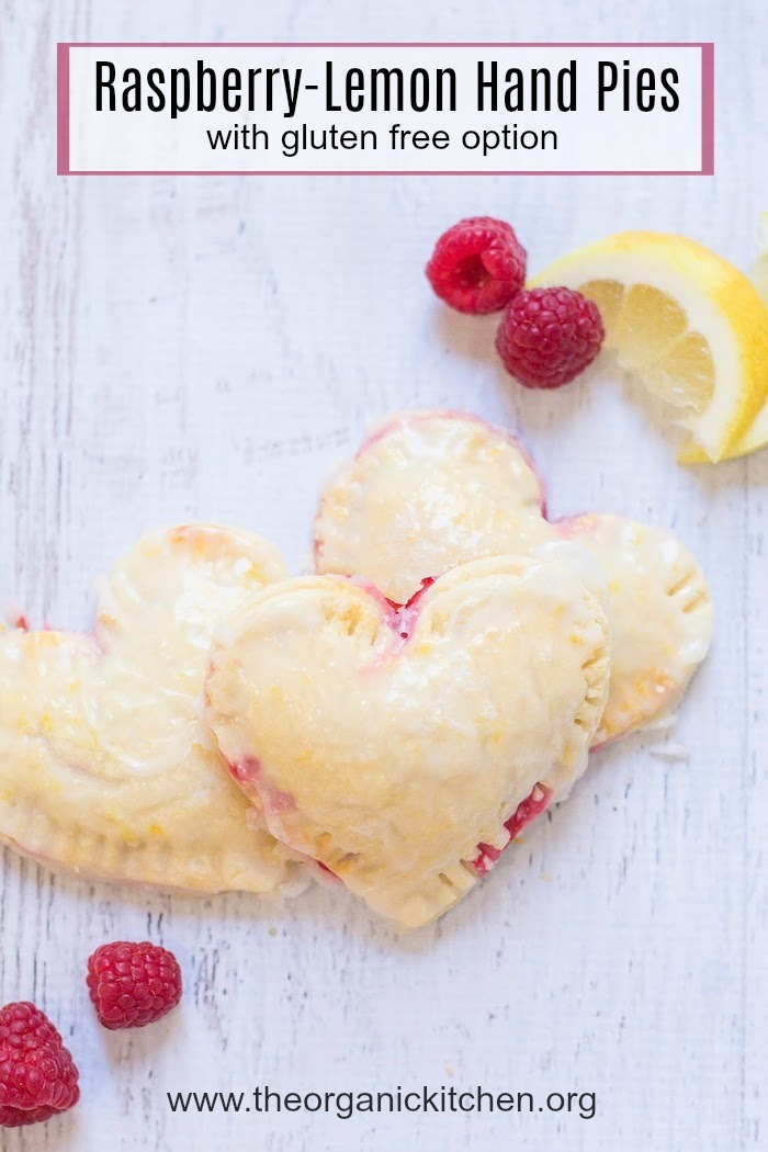 Heart shaped Raspberry-Lemon Hand Pies surrounded by raspberries and lemon slices on white background