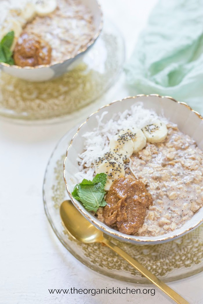 A bowl of Maple, Almond Butter and Banana Overnight Oats on gold laced saucer