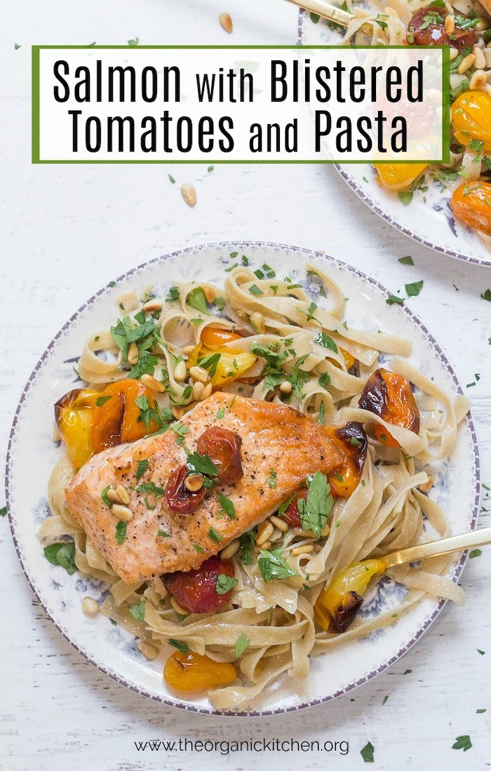 Apiece Crispy Salmon with Blistered Tomatoes and Pasta on a white plate set on a white background