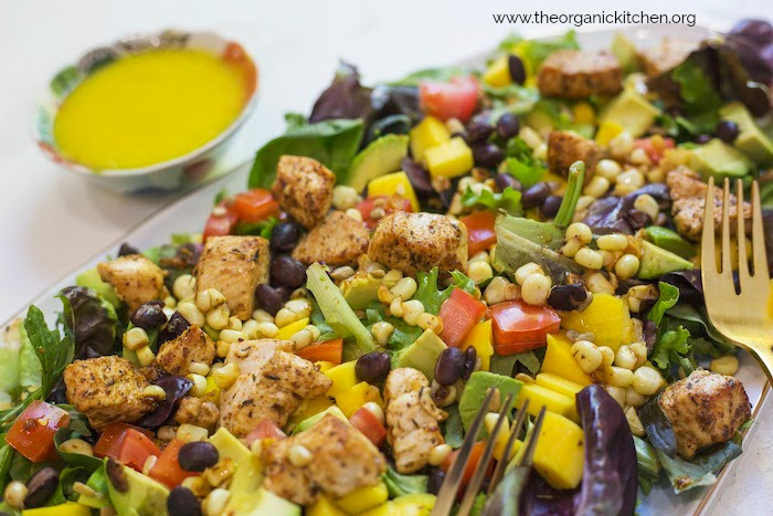 A close up of Southwest Chicken Salad with Mango Vinaigrette showing greens, corn, black beans, diced mango and a small bowl of bright yellow salad dressing