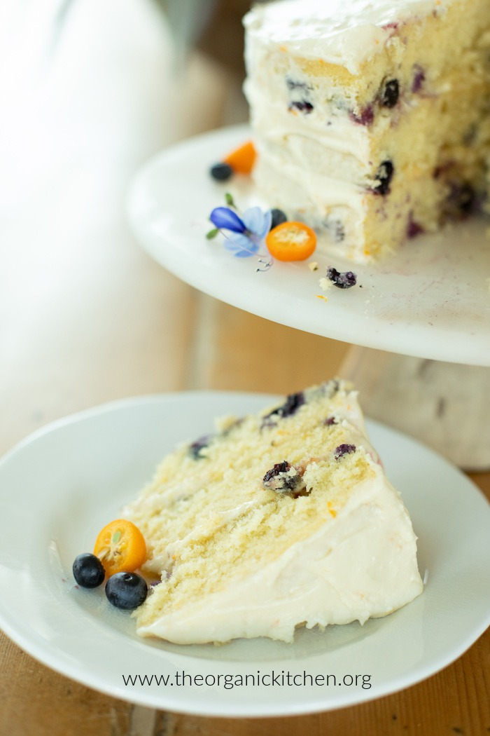 A slice of Orange Blueberry Cake on a white plate set next to a cake plate with the rest of the cake