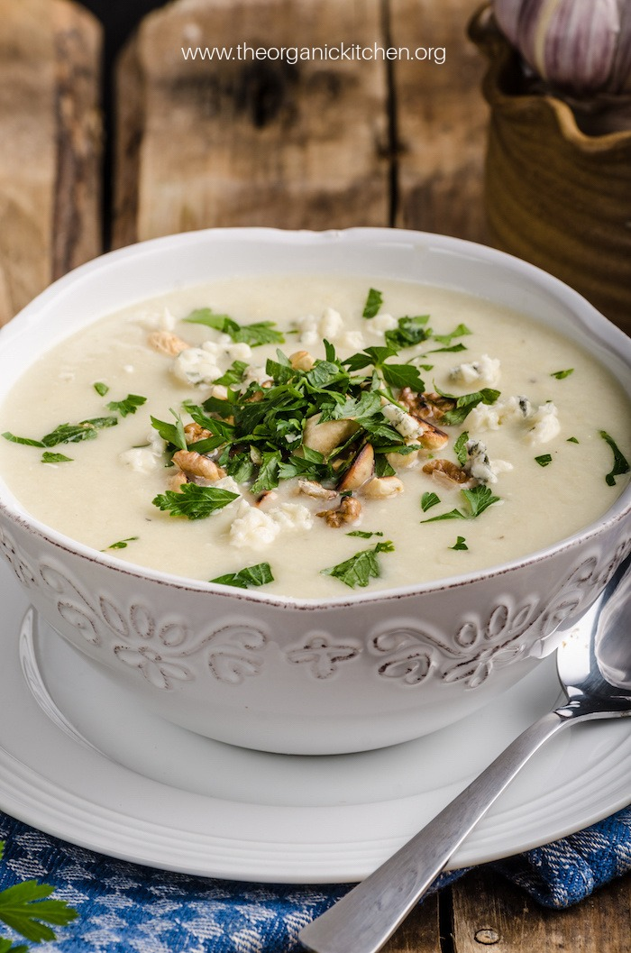 A white bowl sitting on a saucer filled with Roasted Cauliflower Soup garnished with herbs
