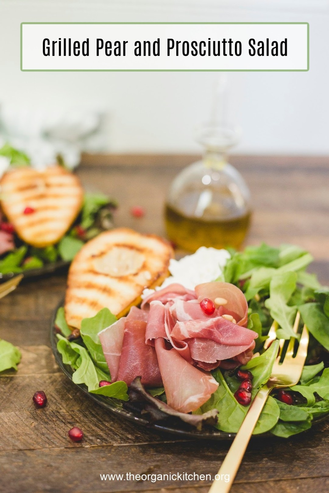 Grilled Pear and Prosciutto Salad garnished with pomegranate seeds on plate with gold fork