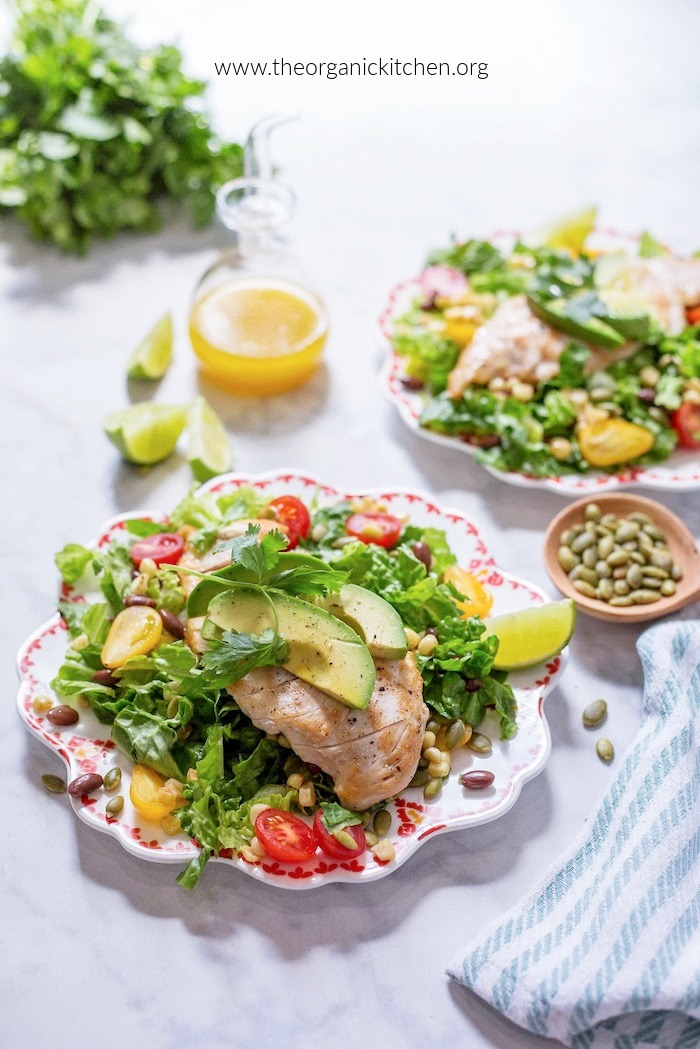 Southwest Chicken Salad with Citrus Vinaigrette with lime wedges, avocado and pumpkin seeds