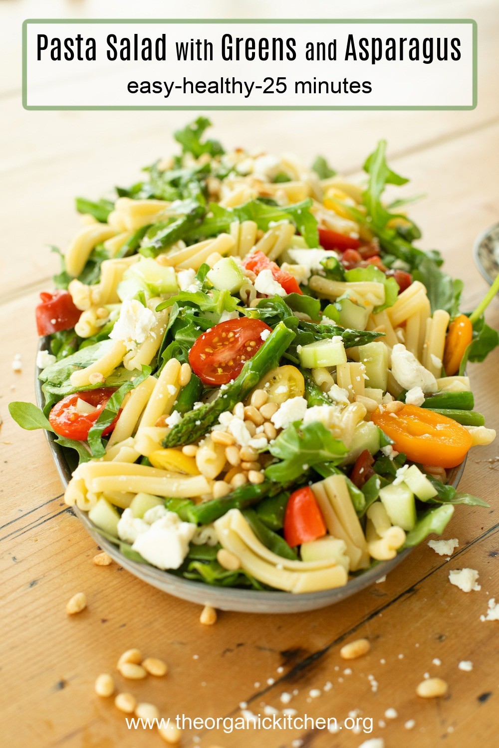 A platter of Pasta Salad with Greens and Asparagus garnished with pine nuts and feta