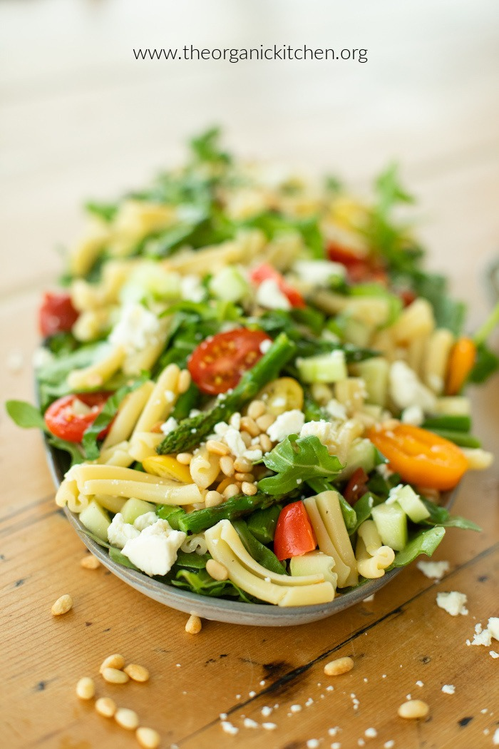 A platter of Pasta Salad with Greens and Asparagus on a pine table