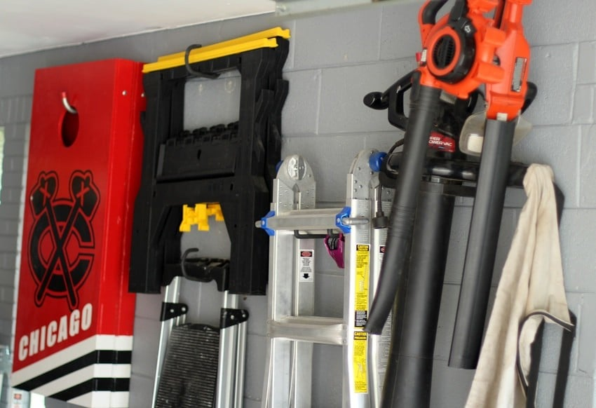 Garage items hanging on wall with hooks to demonstrate how to organize miscellaneous items #garage #organization