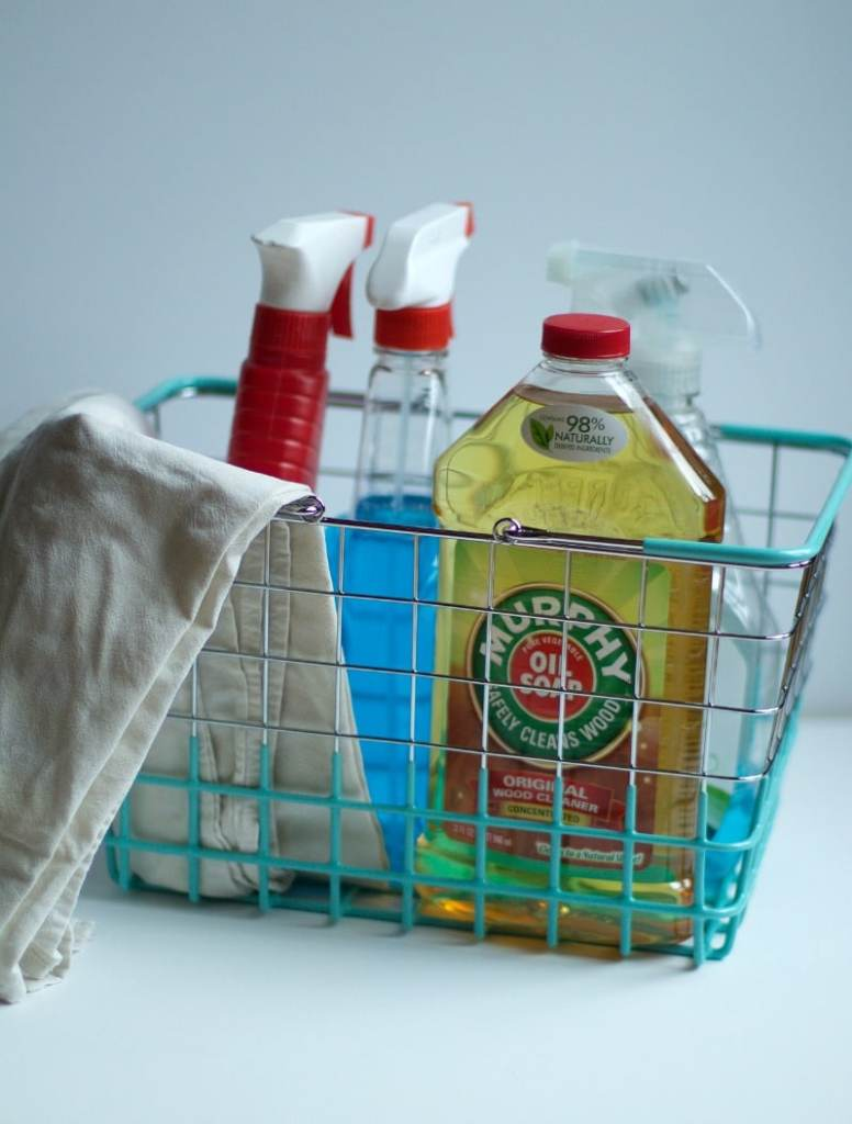 Four bottles of cleaning supplies placed in bin with handles and a rag lying over the side of bin to demonstrate how to organize miscellaneous items #cleaning #organizing