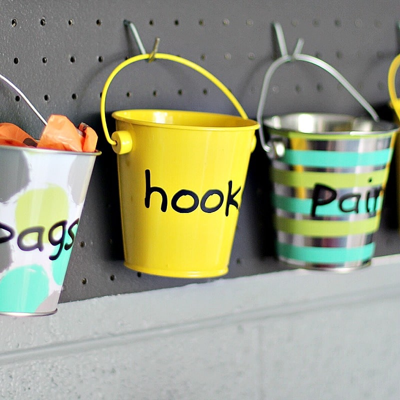 garage pails on pegboard to hold hooks and dog bags
