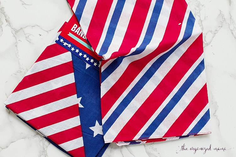 This easy no-sew tutorial shares how you can create a DIY Patriotic Bunting using bandanas and twine from the Dollar Store. #patriotic #fabricbunting