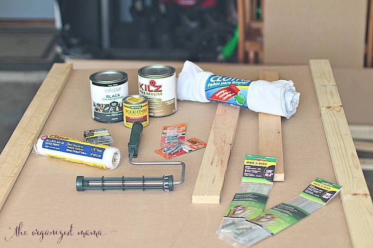 all materials needed to create simple extra large chalkboard including MDF board, stain, chalkboard paint, and finishing nails