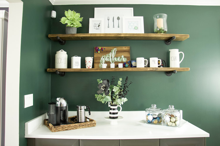 Open shelves made of dark wood against a moody dark green wall along with white countertops and grey cabinets. #ktichen #coffeestation
