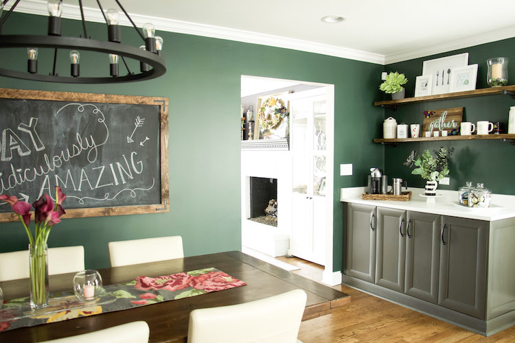 Kitching and dining room in dark, moody green color against dark moody purple color of living room. Dark kitchen space creates a cozy feel. #kitchendecor #modernfarmhousedecor